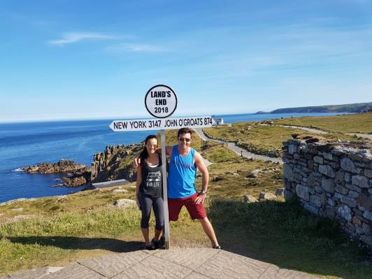 standing at Land's End sign (not the big sign.. you have to pay to take a picture with the bigger one)